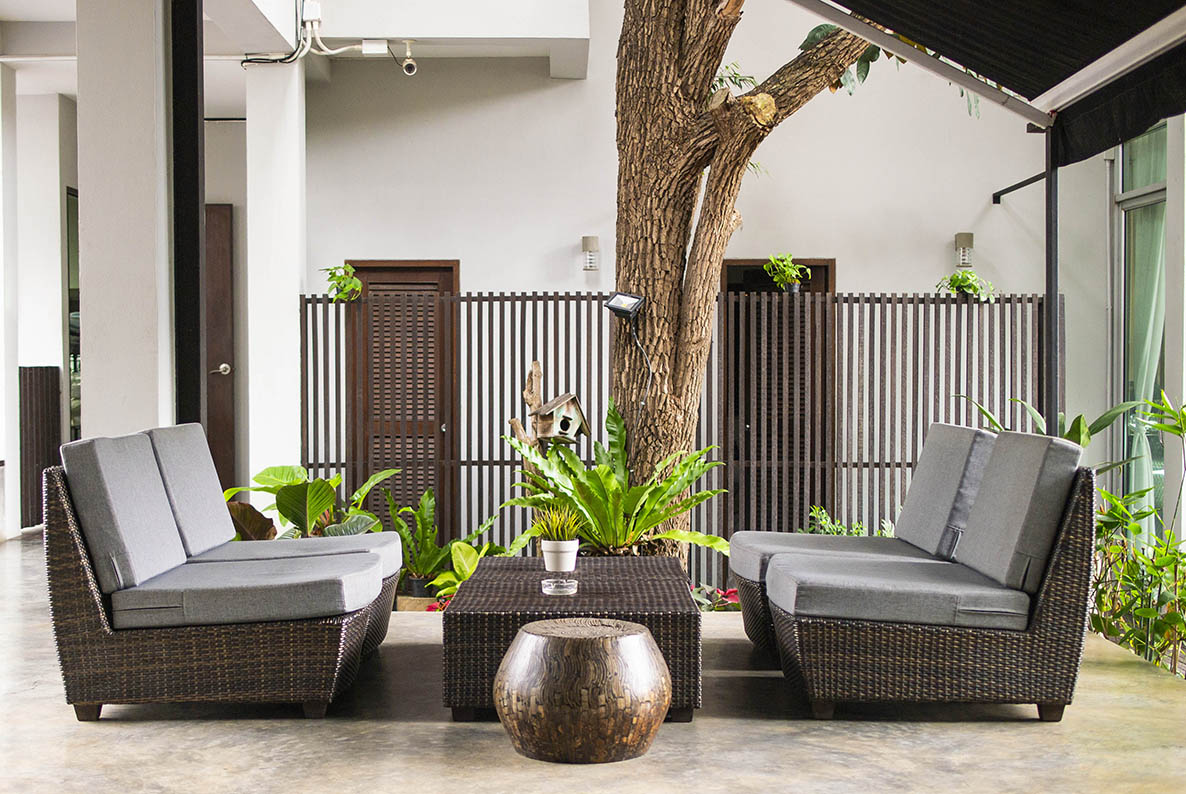 Wicker sofa with pillows and table standing on garden terrace by