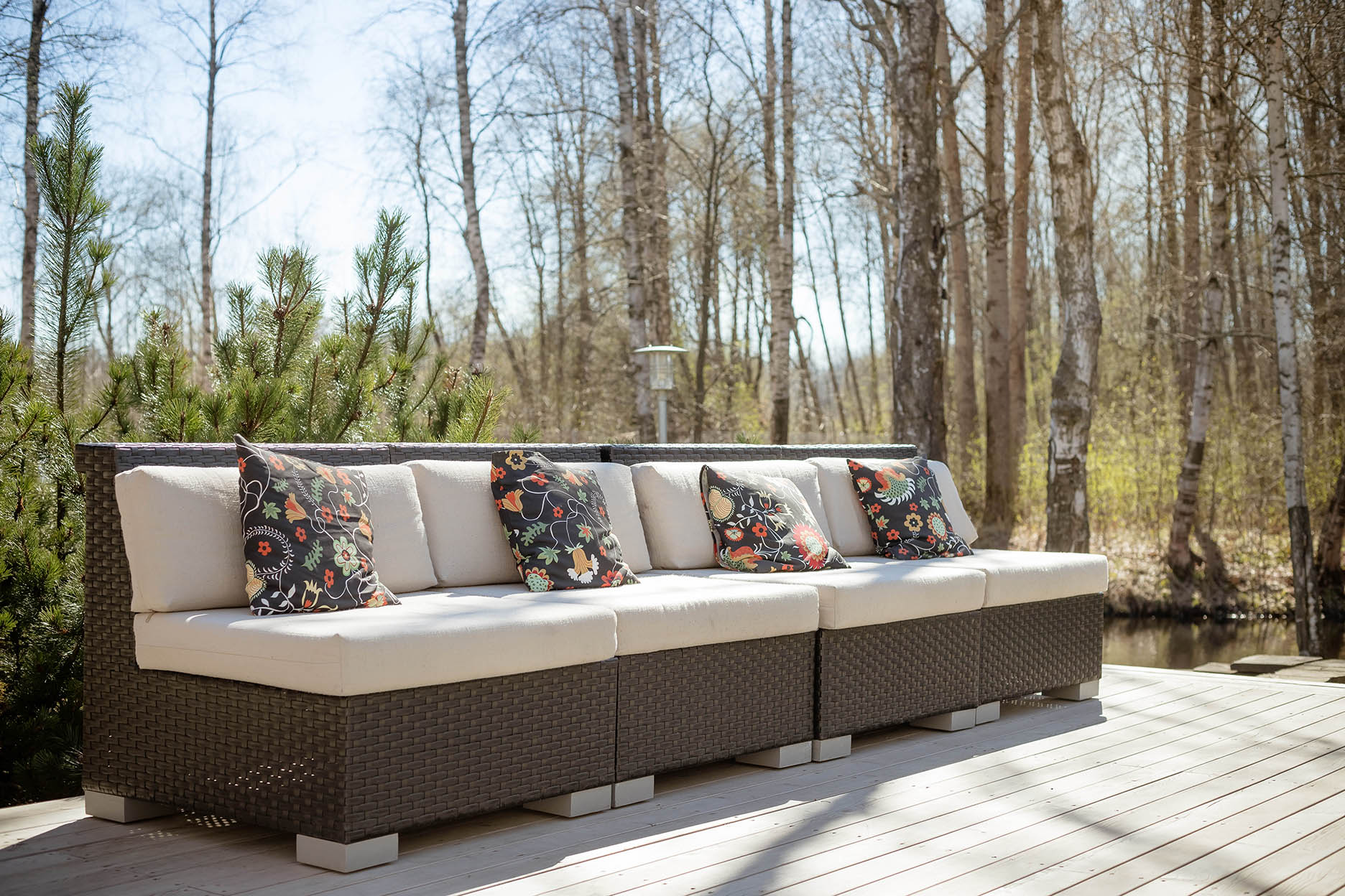 Large terrace patio with rattan garden furniture set.Wooden garden lounge chair with cushion. comfortable rattan sofa. relaxing area outside .patio with furniture on wooden floor.relaxation on the terrace